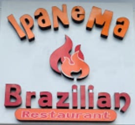 Ipanema Brazillian Restaurant sign with orange and red lettering and a fire logo in the middle of the sign.